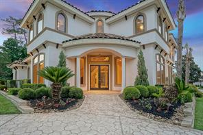 Grand entry with circle stamped concrete drive, double doors, wrought iron details, and a 2 story rotunda just on the other side! Note the attention to detail in this home: tile roof, stucco with corbels and window casings, detailed landscaping.