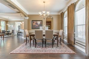 The dining room is large enough for a banquet and features deep crown molding and special picture frame molding. Notice the gorgeous wood like tile flooring and elegant chandelier.