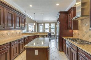 The gourmet kitchen is a cook's dream with sweeping counter tops, gas cooktop, large sink, and premium appliances. Notice the open floor plan and beautiful flow of the home!