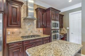The kitchen features a Thermador hood vent, a full complement of appliances, and a built in desk area.
