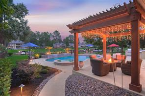 Here we see an evening view of the back yard entertaining area and pool. Note the inviting pergola sitting area.