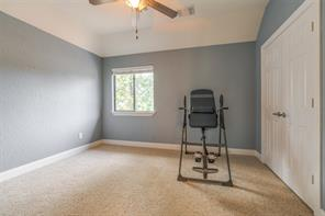 This room is being used as a home gym.  Notice the vaulted ceiling, ceiling fan, and large closet with double doors!