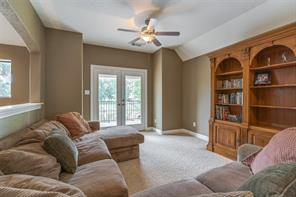 The upstairs game/media room enjoys neutral decorator colors, a ceiling fan, and French doors leading back to the outdoor landing.