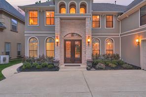 The front entry features stone detailing and double doors with wrought iron accented glass.