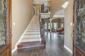 The stairway makes a grand first impression. We also catch a glimpse of the living room in this photo.