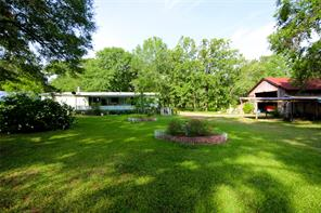 Home sits on 4 acres, 3/2/2 car carport. Property offers a pond, storage shed, pet pen and a cedar barn. The back porch entrance has a handicap ramp. The cedar barn is to the right with the carport.