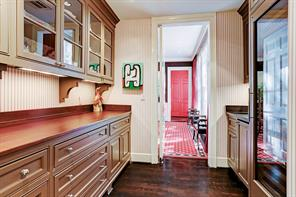 The butler's pantry connects the dining room and kitchen area. A Subzero wine refrigerator to the right with glass doors and two cooling zones, under counter ice maker and china and glass storage make this butler's pantry a useful set up for entertaining.
