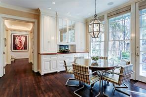 Breakfast room overlooks the back patio and yard through the floor to ceiling windows. The built-in cabinet and drawer storage has a cherry wood counter top with mirrored glass cabinets above.