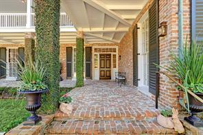 Brick porch to entry with vine covered brick columns.