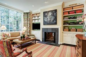 Cozy family room with built in book/display shelving flanking fireplace. The large bay window overlooks the back patio and yard.