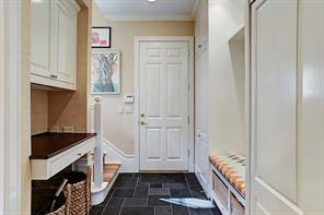 Mud room is off family room and has an additional Subzero refrigerator, built-in desk, bench seat and access to garage and back stair.