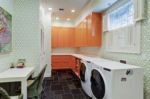 This bright and cheery utility room makes doing laundry fun.  Another powder bath is found to the back left.