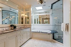 Master bath with marble counters, jacuzzi tub and glass enclosed shower.