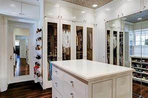 Custom closet with glass front cabinets, three additional closets with mirrored fronts and packing station with 7 storage drawers.