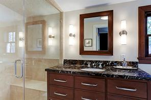 En-suite bath for bedroom #3 with marble counters and frameless glass shower with bench seat.