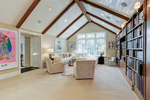The upstairs family and media room features a paneled and beamed raised ceiling, and views to yard. A home office with built-in desk is located off this room.