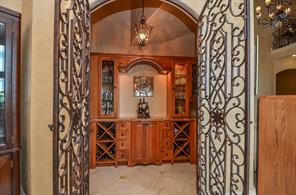 Wine Room - enter through these beautiful ornate double wrought iron doors.  Features a wine cooler, beautiful marble counter tops and a bar sink.