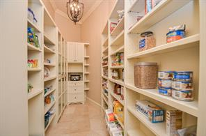 Huge Walk-In Pantry featuring custom shelving and two chandelier light fixtures.