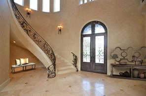 Enter into the 2-Story Foyer with a 5' radius dome with faux finish showcasing a beautiful chandelier with motorized lift system.  The Grand staircase boast travertine treads and features award winning custom iron work.  Mediterranean profile that is sure to impress.