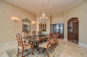 Formal Dining area features a Swarovski crystal chandelier and wall sconces. Wine room and Buffet area access from Dining area.
