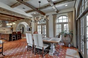 The breakfast room is spacious and light filled.  Patio access to the right and open to the kitchen to the left, this room is stylish with its own tile pattern different from the kitchen and living room.  The reclaimed wood beams extend into this space creating continuity with the kitchen.