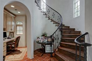 A nice office nook resides off of the breakfast room and second staircase that access the second floor.  To the left of the picture is the elevator, half bath, laundry room, access to your 3-car garage, and additional french doors leading to the outdoor kitchen/living space.