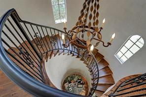 Looking down from the second floor landing of the rear staircase, you can appreciate the elegance and style put into this design.  Plaster walls, iron railing that matches the main staircase, and plenty of natural light adorn this set of stairs.