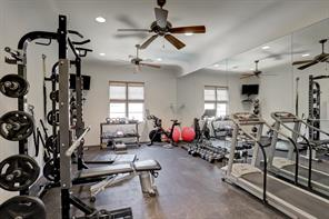 This bedroom is used as a home gym for the owners.  As you can see, its a huge space and can hold several large pieces of gym equipment.  Two ceiling fans help keep the air flowing in the space.  The window overlooks the backyard and pool.  You also have a TV to catch up on the news, favorite shows, or workout videos.  This room has a spacious en suite bathroom and closet.