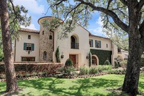 An alternate view of the home shows the stucco and stone finishes and classic tile roof.  To the left behind the shrubs and stone wall sits a tranquil private patio space off of the library/home office.  The stone tower houses the spiral staircase leading to all three floors off of the main entry.  Massive wood front doors, imported from Mexico, really accentuate the custom details to this fine home.