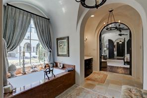 A massive soaking tub overlooks your pool and backyard and sits across from the separate master shower.  The arched doorway connects to the master bedroom.  This space truly encompasses that resort style elegance that would be a joy to experience everyday.