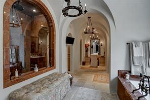 Another view of the master bathroom details the elegance of the space.  Look at the architectural design of the archways along the length of the room.  To the left is a huge walk-in shower with multiple heads.  Straight ahead is a quaint makeup station that is flanked by the two walk-in master closets.