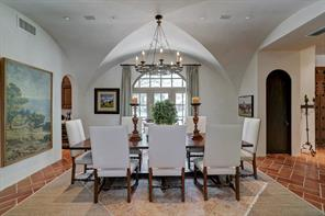 An alternate view of the formal dining room, you see the windows facing the front yard, groined ceiling, plaster walls and terra-cotta tile floors.  The door on the right is another half bathroom.  Through the archway to the left is a butler's pantry with dishwasher, beverage refrigerator, sink, matching concrete countertop with the kitchen, and wine closet.