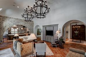 An alternate view of the living room shows you the openness to the kitchen as well as the foyer and front doors.  beautiful floors, stylish chandeliers and soaring ceiling complete the homey space.