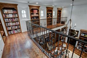 The second story library bookshelves wrap around the library/home office below. Decorative iron railing complement the wood floors and chandelier.  The room below has ample storage space with it's finely crafted cabinetry.  The closed door on the right of the picture leads to the master bedroom entrance hall.