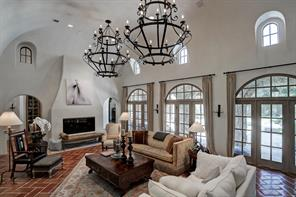 Curved lines to the high ceilings accentuate the design.  Two large iron chandeliers, Segreto plaster walls, terra-cotta tile floors in a herringbone pattern, double-sided fireplace, and french doors leading to the covered porch and your backyard oasis.  This room gets plenty of natural light and opens to the kitchen.