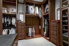 One of the two master closets, this closet wraps around to the left.  Multiple built-in dressers and custom cabinetry create a clean and well organized closet.