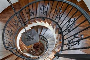 Taken from the third floor landing, this staircase is the one housed by the stone tower see from the front of the home.  Beautiful iron railings, hardwood steps, and subdued chandelier create a functional and stylish design.