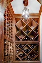 This wine closet hold approximately 200 bottles and has cabinet storage below the racks.  Not seen is the imported door to the room from Mexico.  Very stylish and plays well with the similar front doors.