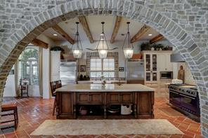 There is so much to love about this kitchen.  Looking in from the living room, an arched brick entry provides that rustic detail along with the reclaimed wood beams and brick coping around the windows.  The tile floors run throughout the first floor living spaces.  Aside from the beauty, this is indeed a cooks kitchen equipped with Viking Professional series refrigerator and freezer, plus a Viking Professional series double oven with 6 burner gas cooktop, griddle and grill.