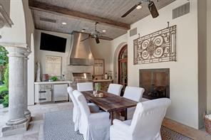 This view of the outdoor kitchen shows you a few of the air conditioning vents above the fireplace.  Elegant wood ceiling and reclaimed wood beams add character and depth to the ceiling.