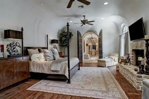 This tranquil master retreat exudes warmth, style and elegance.  The hardwood floors were made from reclaimed pallet wood by Schenck & Company with varying sized planks.  These same floors were installed in the current owner's other home and they were awarded the 2013 woodfloor of the year award.  Segreto plaster continues here and the amazing architecture to the arched doors and walls through to the master bath further illustrate this fantastic design.