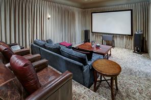 A true theater room, this generously sized space has stadium seating so no one has an obstructed view.  This room is located in the interior of the home so there are no windows.  Nice curtains, wall sconces, and lighting along the steps give that real movie theater feel to the space.