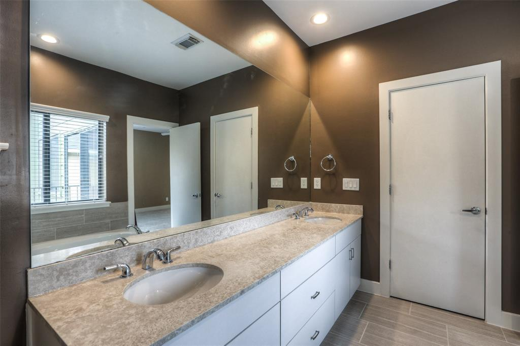 Master bath features dual vanities with granite counter top.