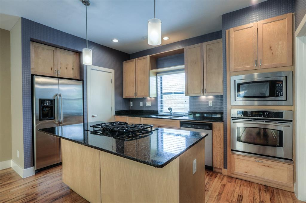 Center island kitchen with granite counter tops, stainless steel appliances and gas cook top.