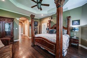 Master bedroom has plenty of space for large furniture, has crown molding, laminate flooring, exterior door and ceiling fan.