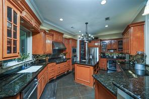 This kitchen has all the bells and whistles for a chef: veggie refrigerator, commercial cook top with pot-filler and hood, Jenn-air convection oven, wine fridge, veggie sink, storage/pantry, stainless appliances, island and breakfast bar seating.