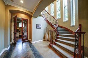 Elegant curved stairway with wood/iron railing leads to extra bedrooms and media room. Note the way the windows follow the stairs.