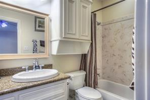 Guest suite bathroom with granite and linen storage.