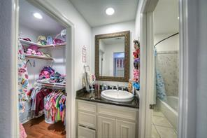 Jack and jill bathroom with granite and separate vanities and closets on each side.