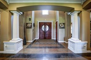 Note the beautiful solid doors, two-toned stained concrete, and two-story entry.